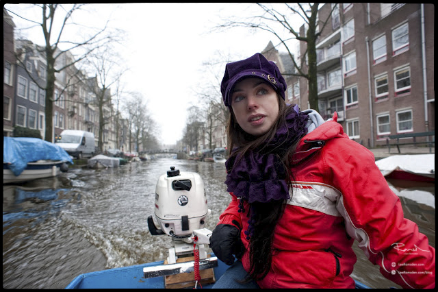 Kelly Moss Lee Ramsden driving boat on Amsterdam Canal out board motor blue boat