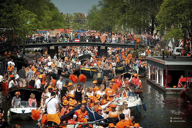 Amsterdam canal geracht queens kings day full of party boats people wearing orange