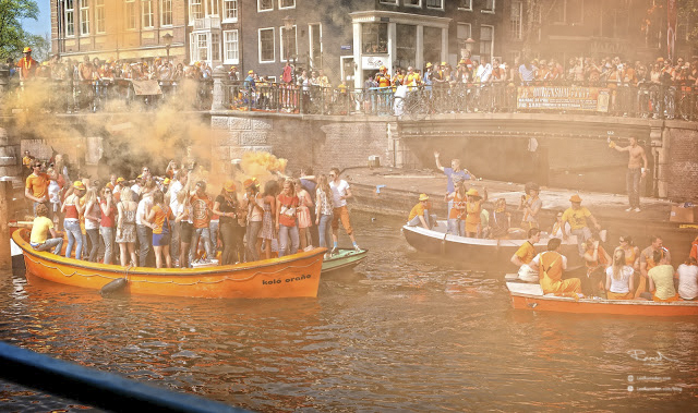 Amsterdam Queens Kings day canal boats orange flare and smoke