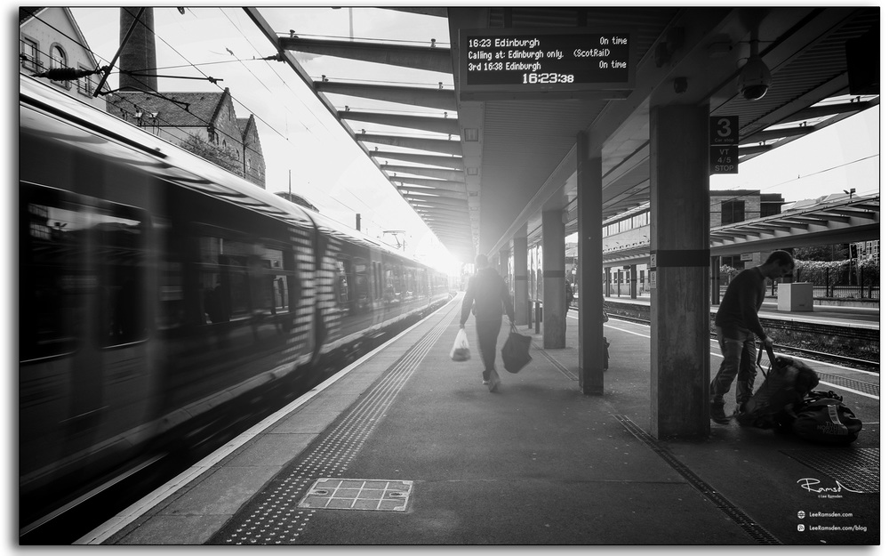06 man with luggage walking along train station platform at Edinburgh waverley