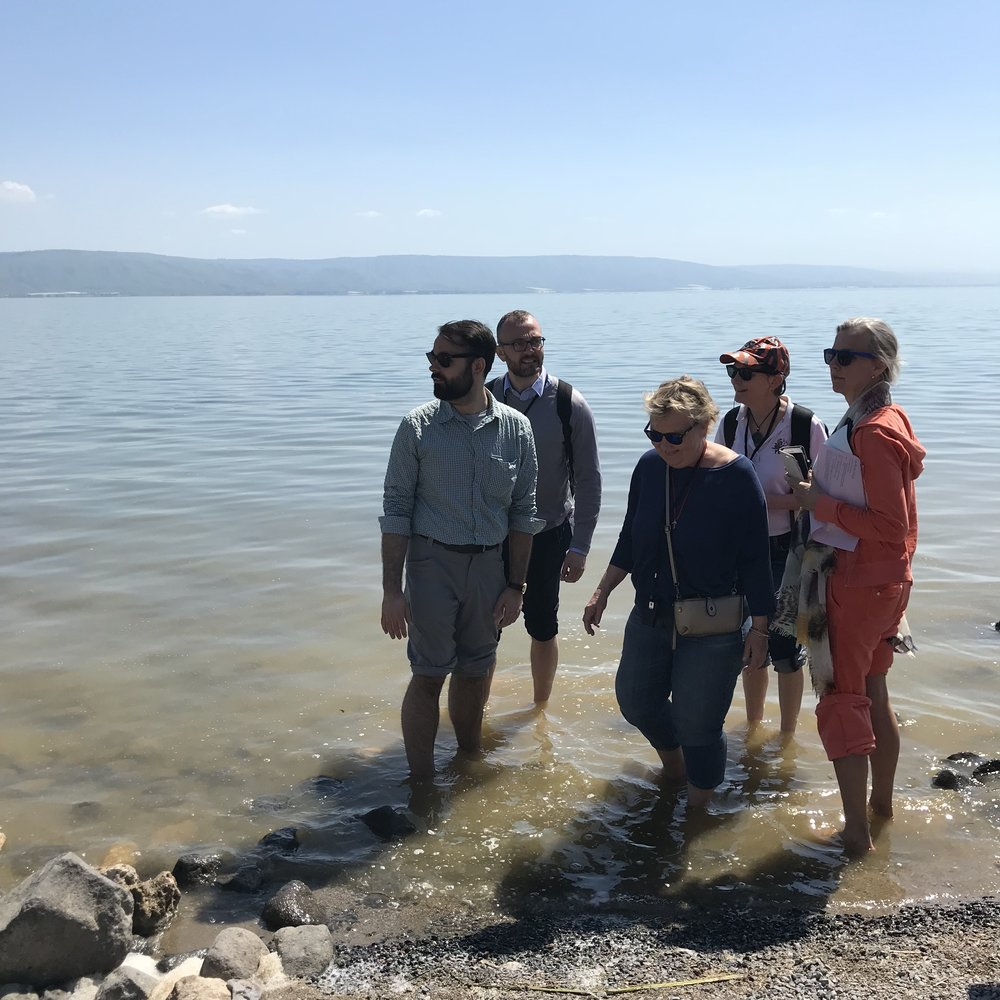 Our pilgrims dipping their hands and feet in the Sea of Galilee