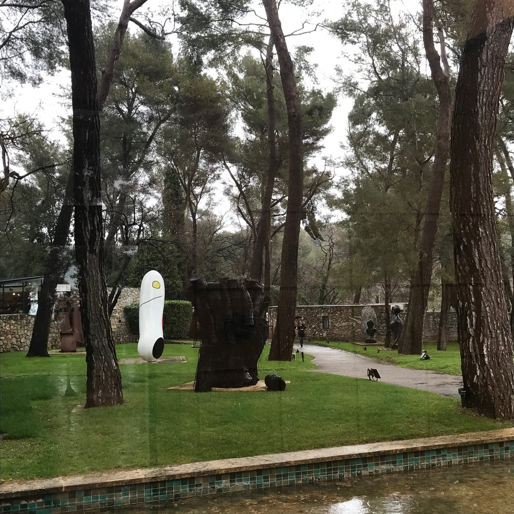 Looking through the window (and the streaking rain) to the Maeght Foundation sculpture garden