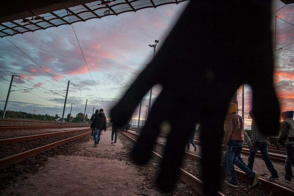 Un migrant m'empêche de photographier alors que ses compagnons s'enfuient sur la voie ferrée menant au shuttle.  L'Humanité - 10.08.15
