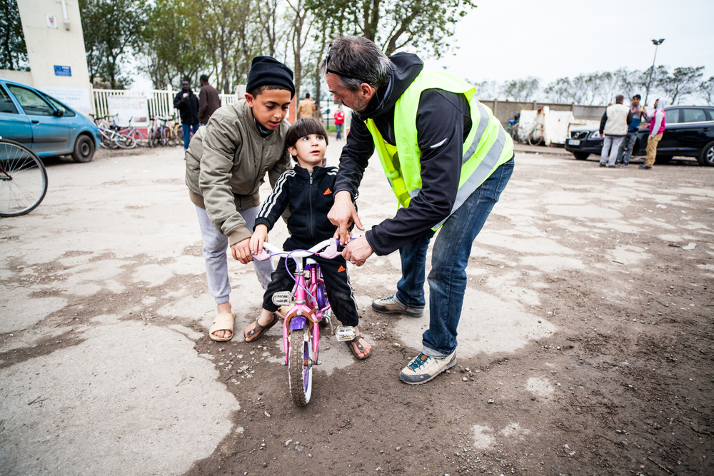 Yann est bénévole sur la jungle. Il travaille comme intermittent sur l'organisation des festivals d'été et autres évènements culturels. Il apprend à un bambin comment rouler à vélo.  Témoignage Chrétien - 23.10.15