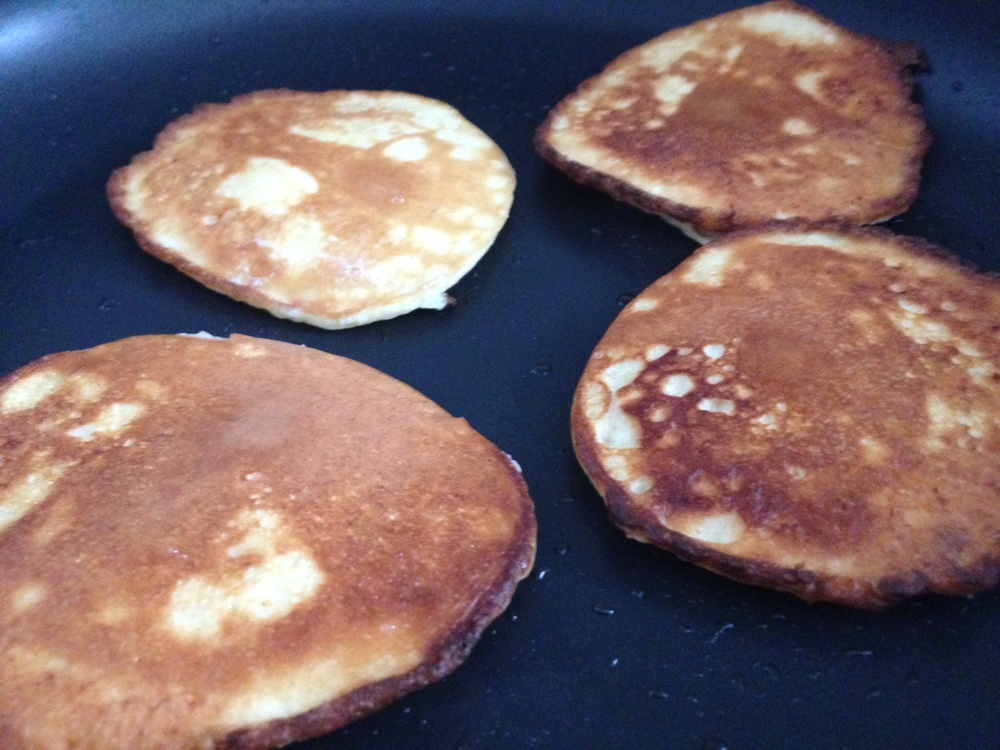 Pancakes frying in coconut oil.