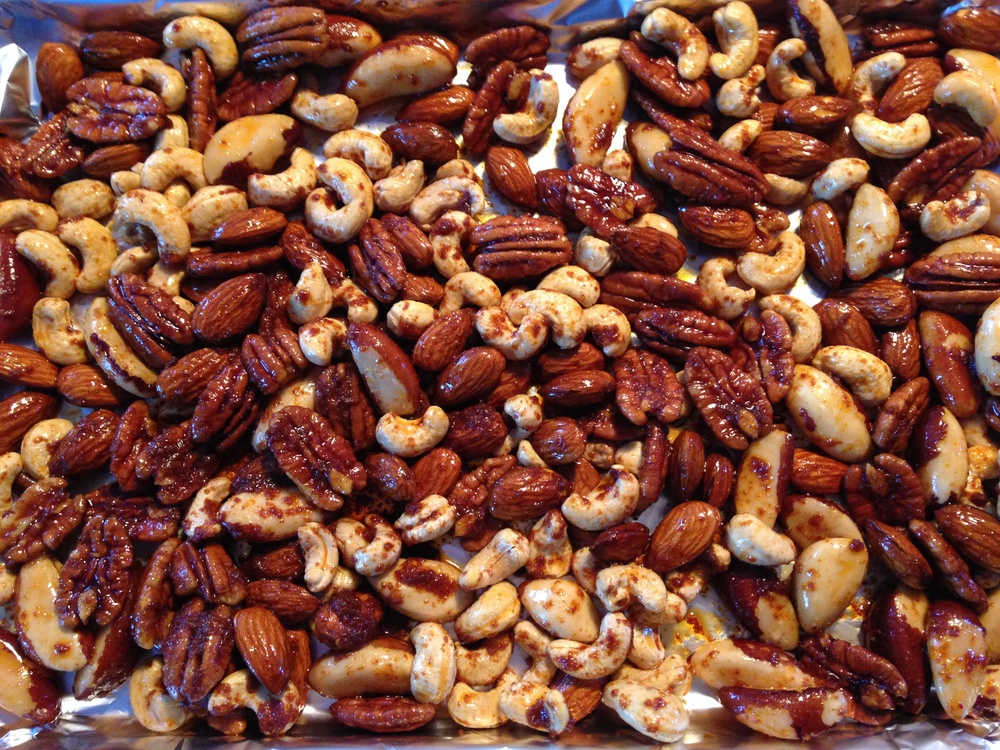 Coated nuts spread on the tray for cooking.