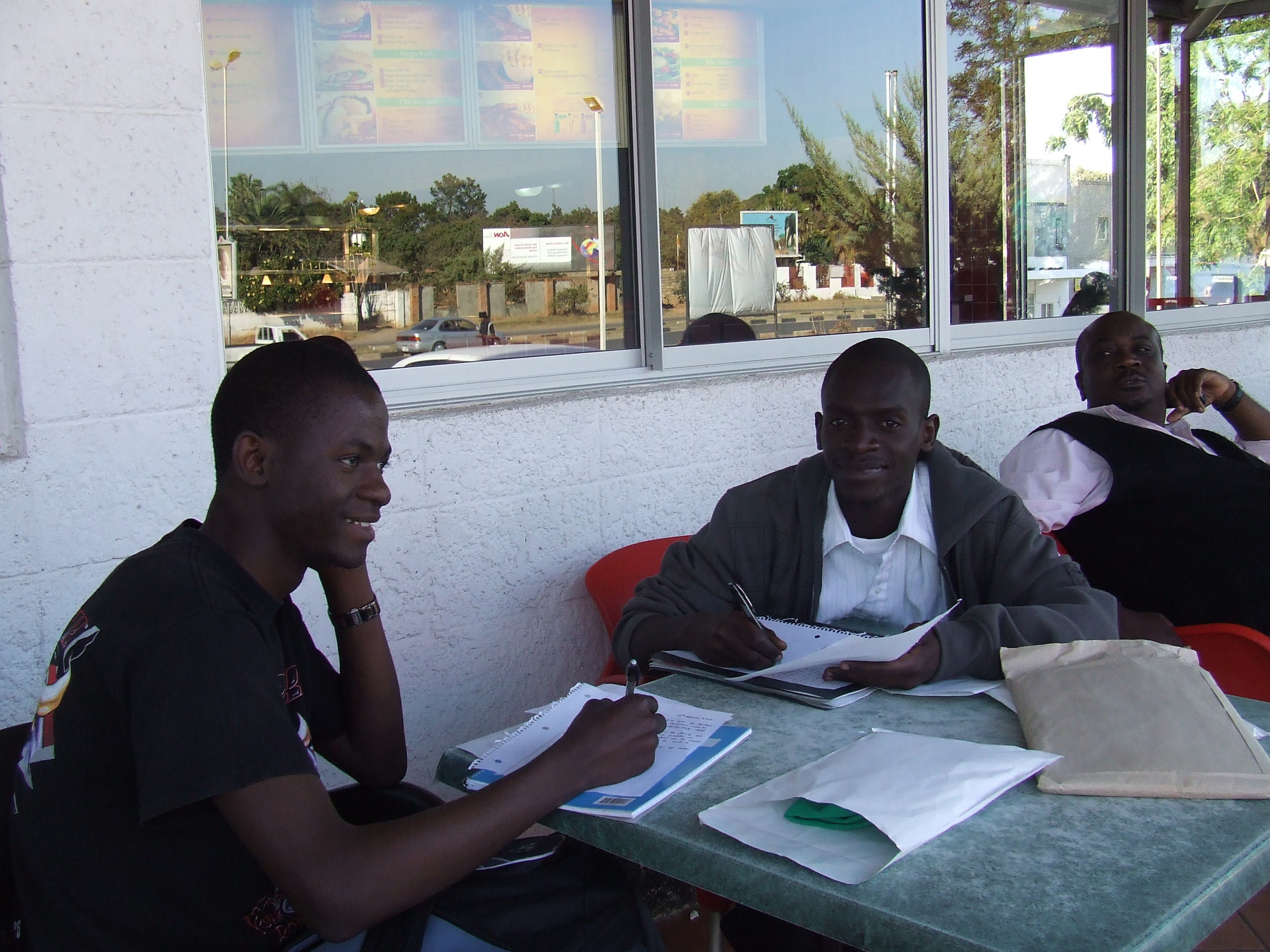 Happy (on the right) writes a letter to his sponsor, Mrs. C.
