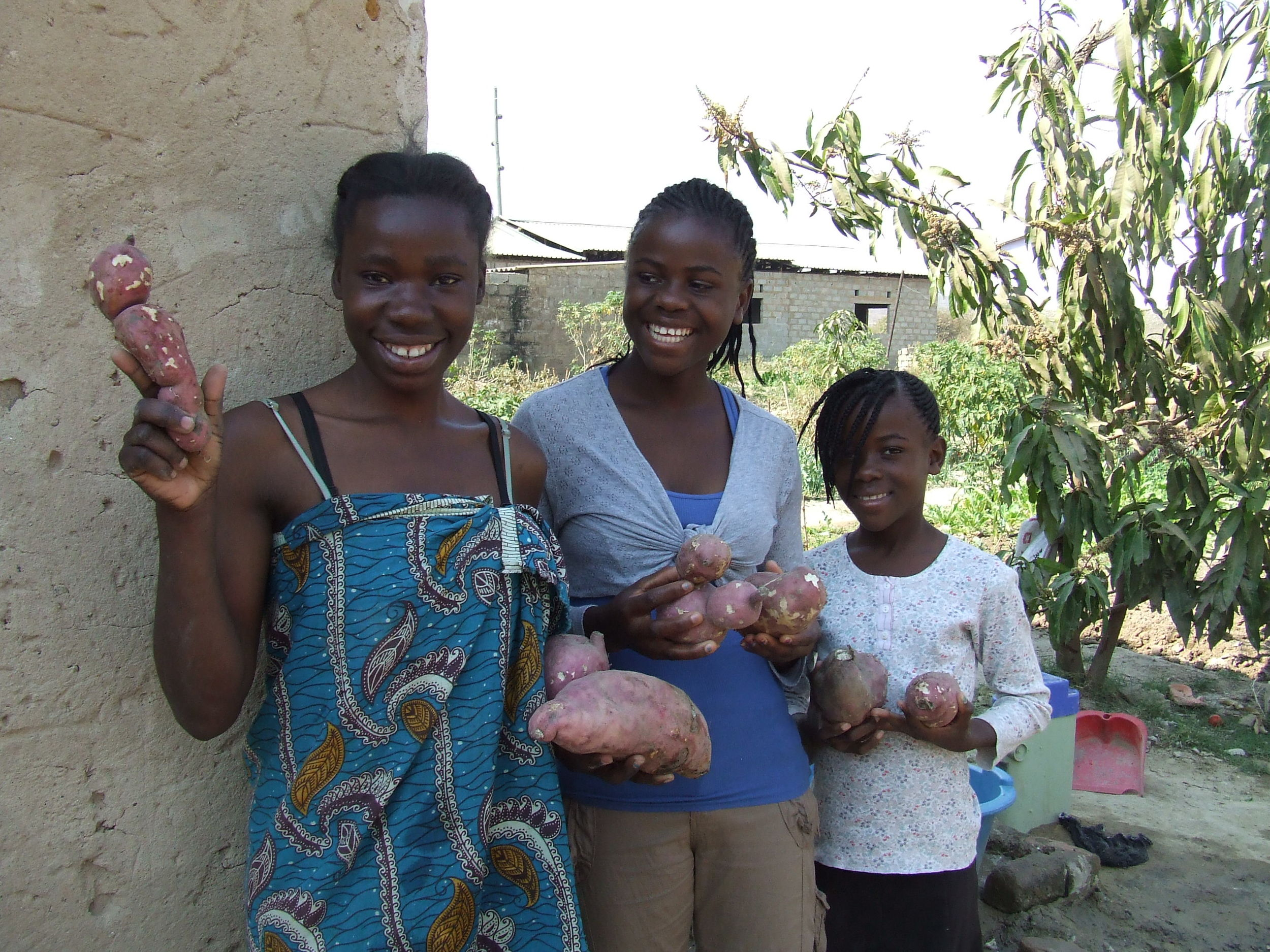 Bertha and two other boarders show off the sweet potatoes grown in the garden.