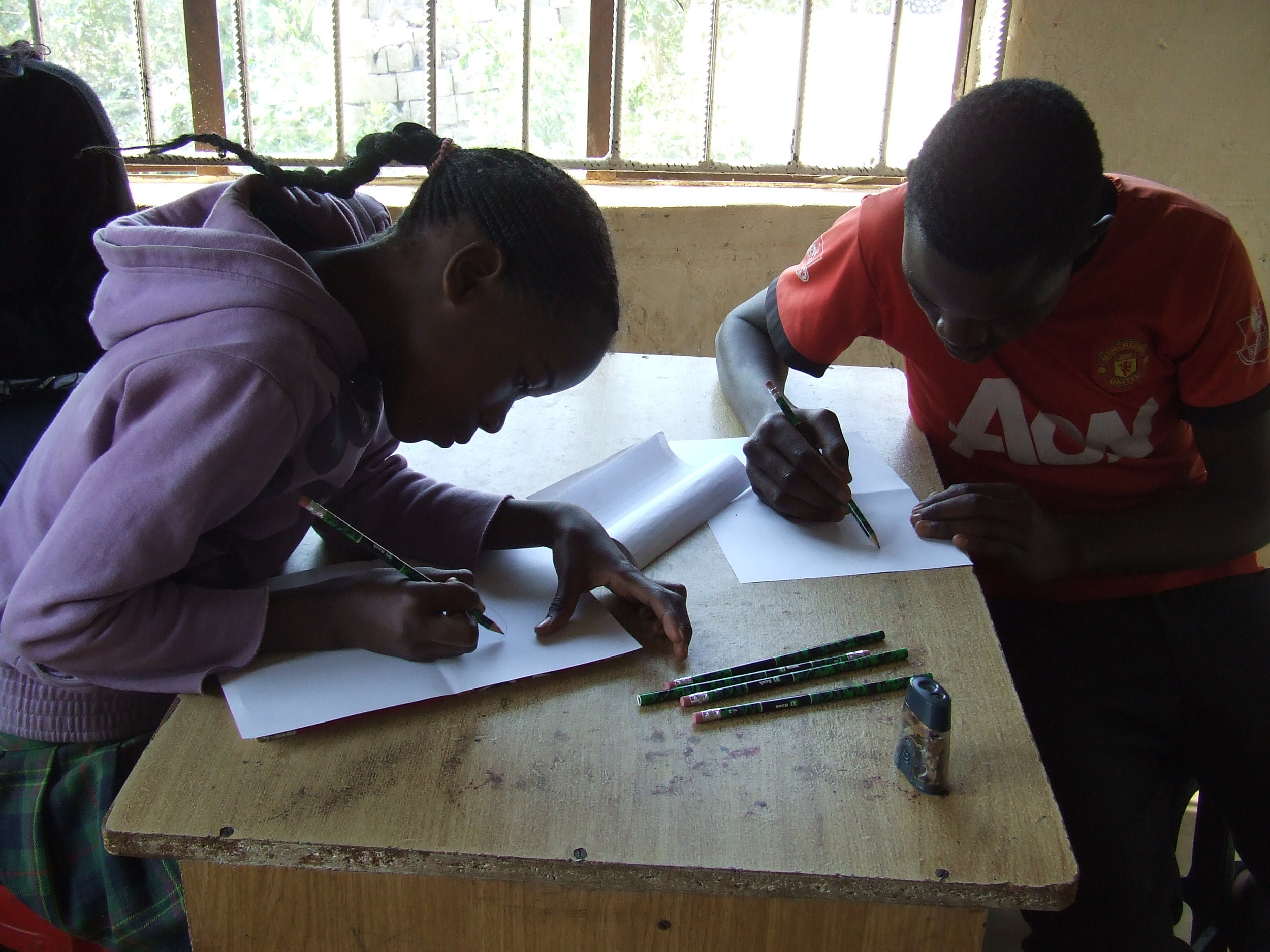 Memory and Kelvin, two AYC members, focus on their letters to their sponsors.