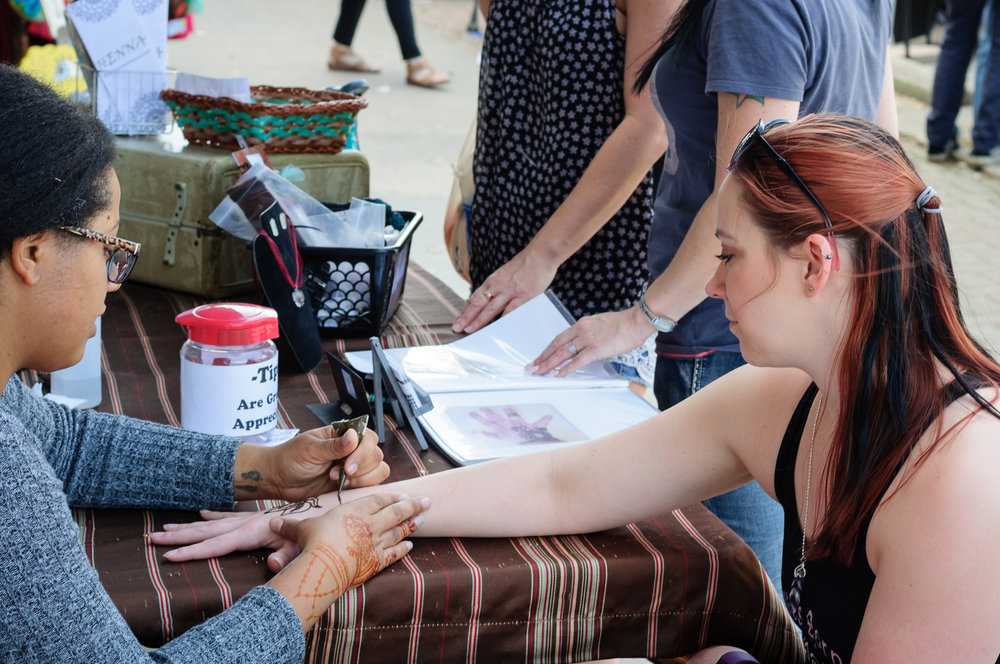 Lydia Pine applying henna tattoos during the event in downtown.  It is a beautiful way to showcase body art without a permanent investment.