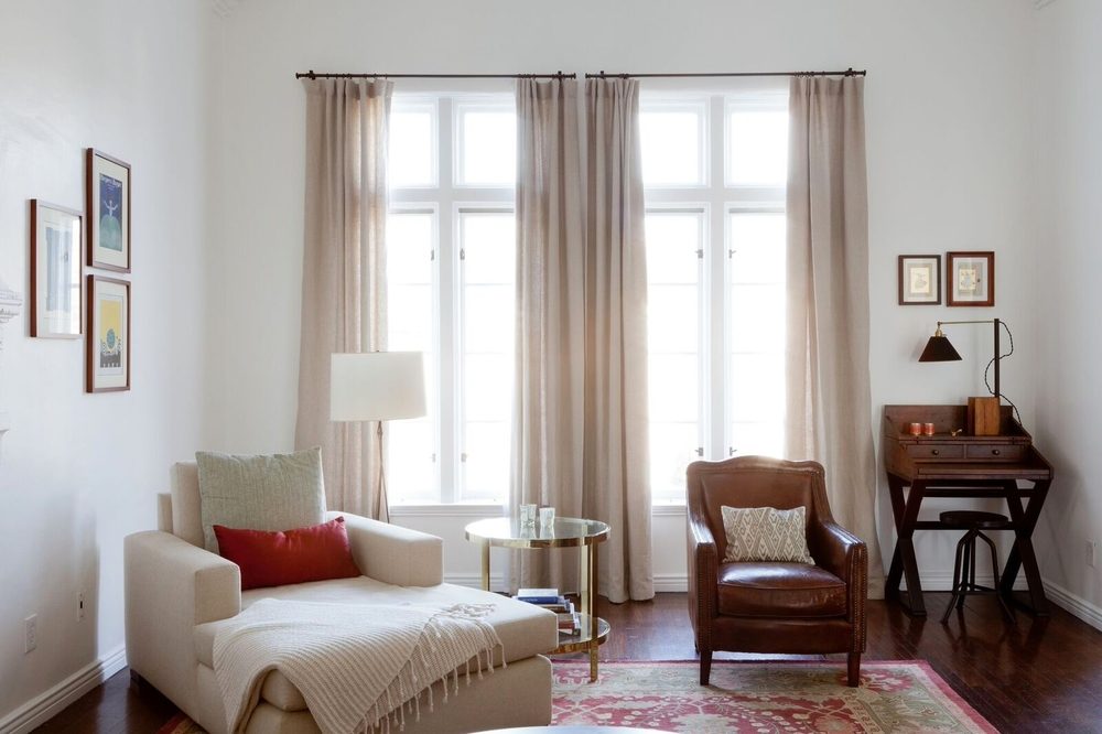 The epic windows in the living room are dressed with natural linen draperies. The chaise lounge is roomy and deep and has become the preferred spot for watching films or binge watching series. A writing desk creates a mini office in a quiet corner.