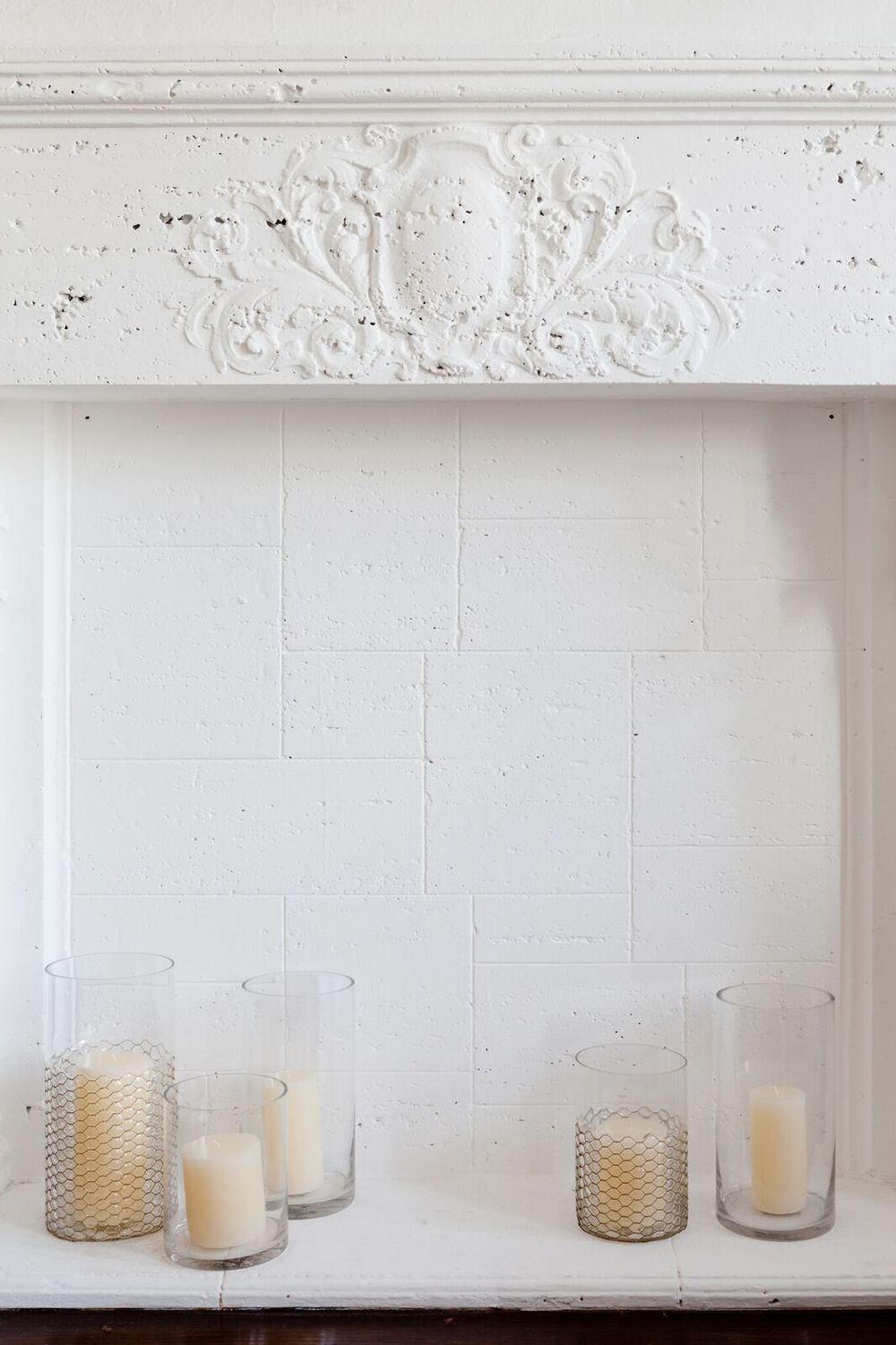 There was so much beautiful detail to the fireplace that I was hesitant to mess it up by adding too much. Simple candles in big glass cylinders (the ones with the chicken wire!) make it glow again.