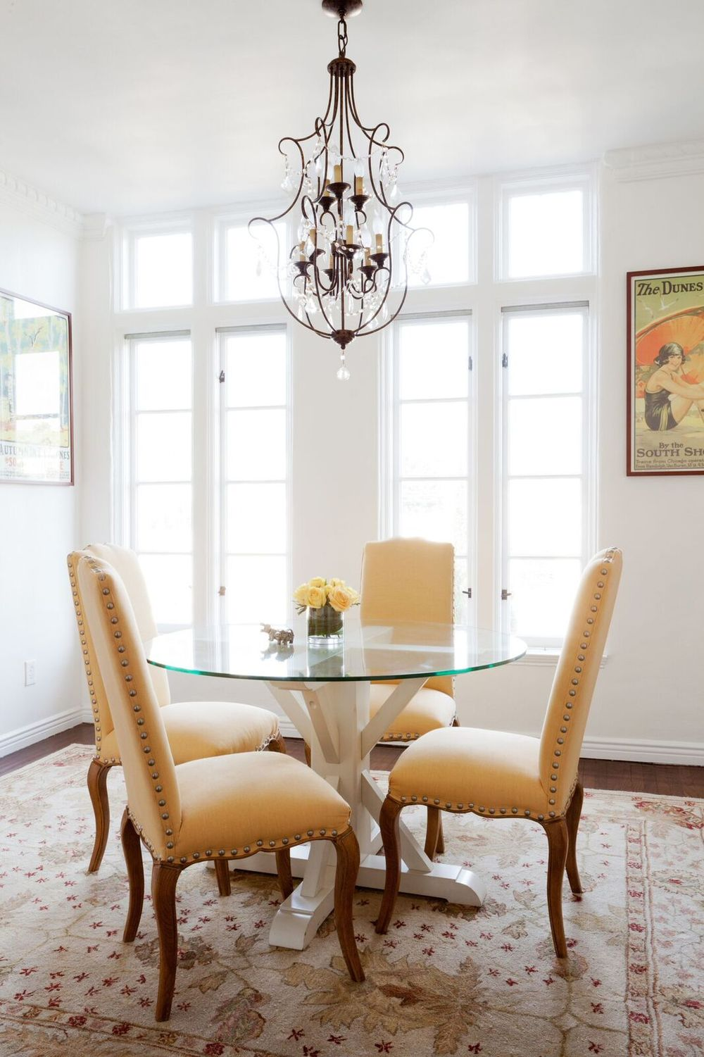 I decided not to dress the windows in the dining room so that it would always be filled with warm light. The chandelier does the job at night. The dining chairs were upholstered in sunny yellow linen that had been used as draperies in the client's previous apartment. An antique (and super soft) rug and four South Shore Line prints finish the space.