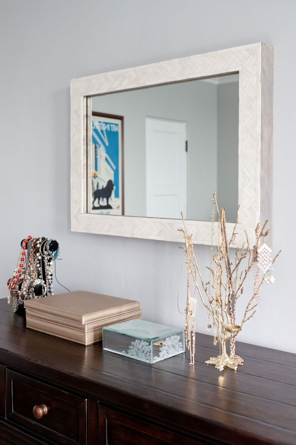 So many pretty details: The mother-of-pearl herringbone on the frame of the mirror, the beautiful jewelry and boxes, the vintage Art Institute of Chicago print in the reflection.