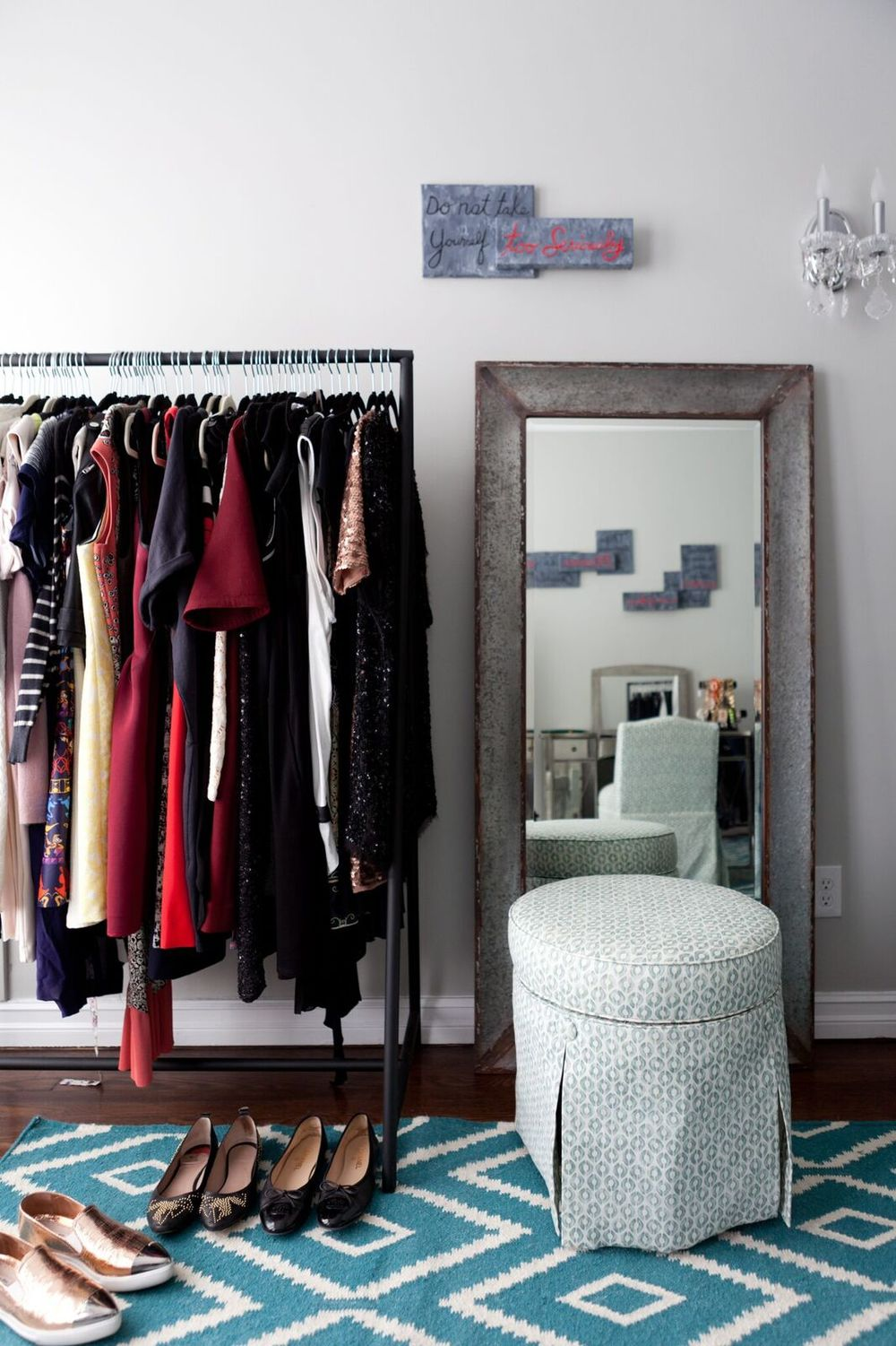 Two more garment racks surround the galvanized mirror on the opposite wall. The graphic art pieces are a perfect reminder, and were inspired by a speech given by my client's beloved grandmother. A tufted pouf (it swivels!) is upholstered to match the vanity stool.