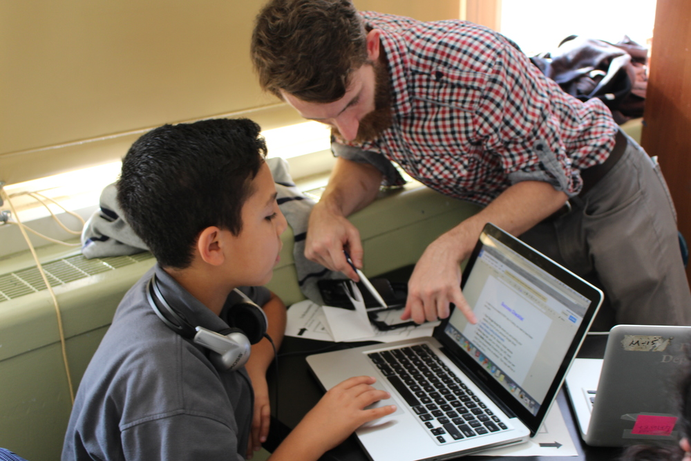 Teacher Jared Sutton provides one-on-one support for a students working on coding.