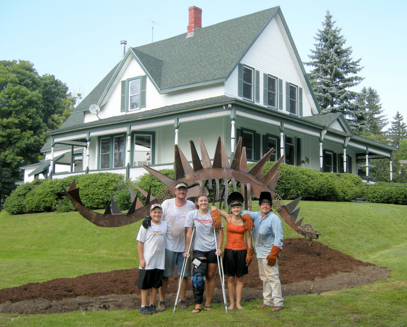 "In 2010, our family worked the entire 4th of July weekend to landscape and then build the famous fiddlehead dinosaur, named ""fern"". The boys did the yard work and the girls welded up the monster!"