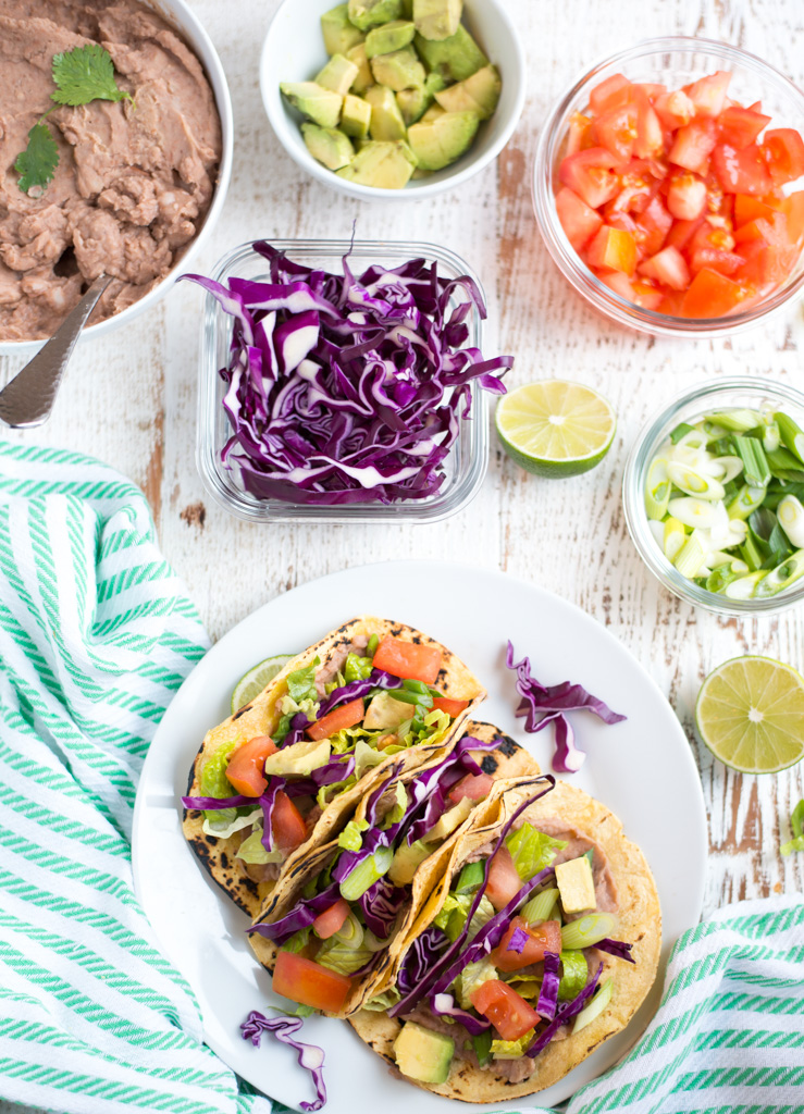 Slow Cooker Refried Bean Tacos recipe. Super fast, so easy and delicious! Perfect for dinner or any meal of the day. Healthy, and naturally gluten-free and dairy-free.