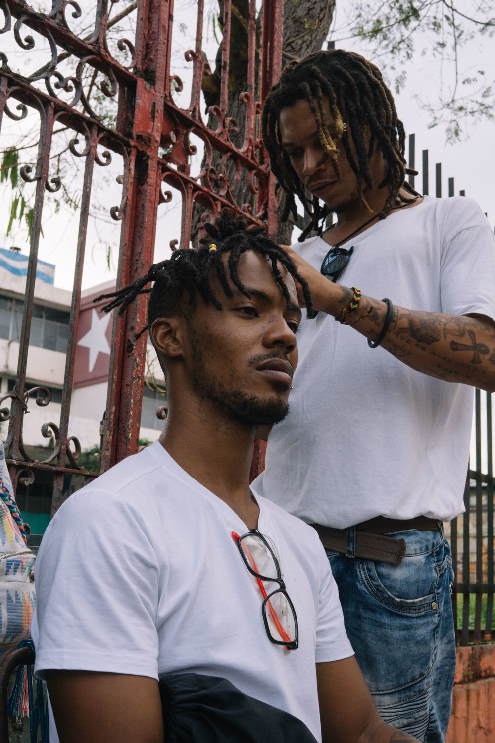 two men re-twisting each other's Locs during a street art festival