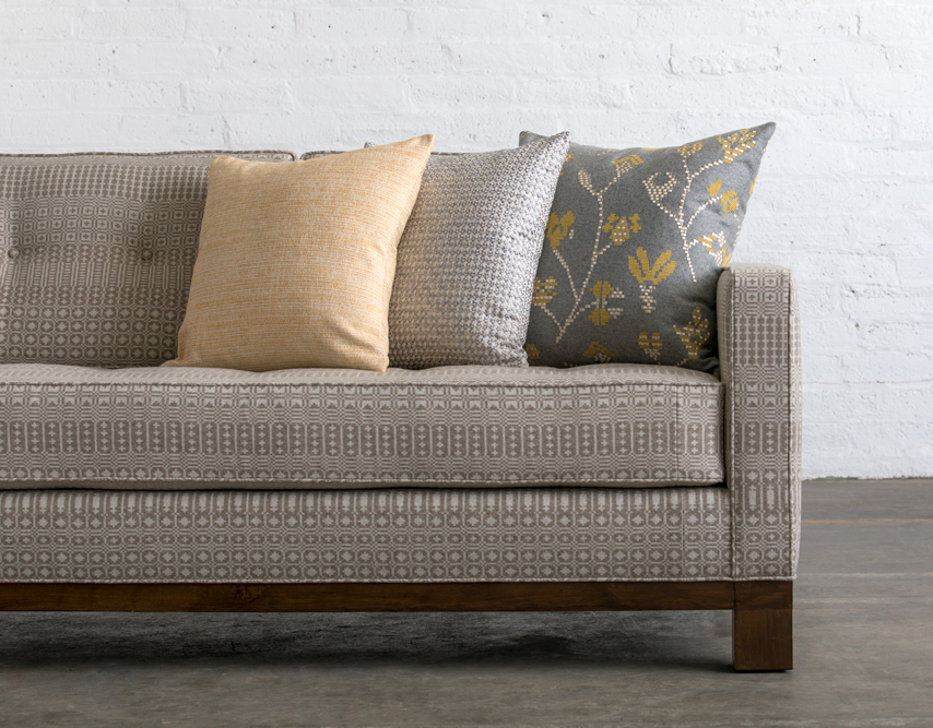 Sofa and cushions upholstered with some of the  Undaunted  collection fabrics.