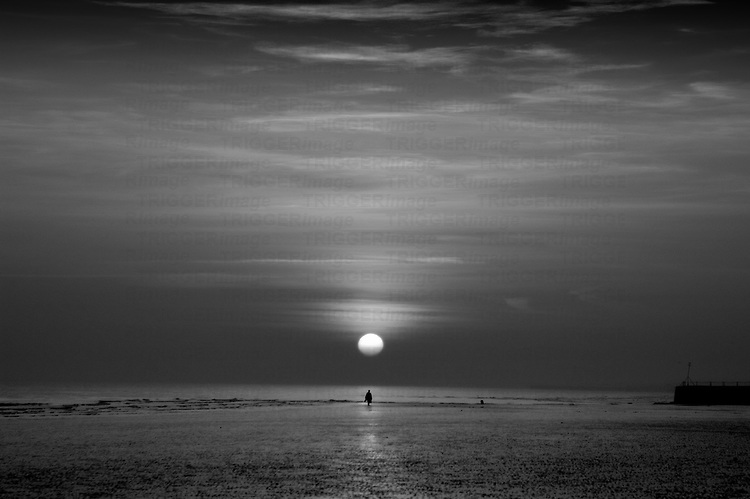 A lone figure in the distance below a setting sun on a deserted beach