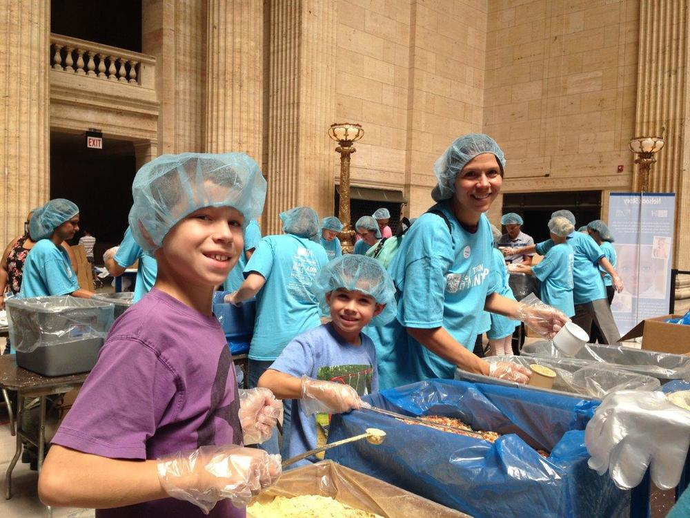 Volunteers help to pack hundreds of meals for distribution through Feed My Starving Children.