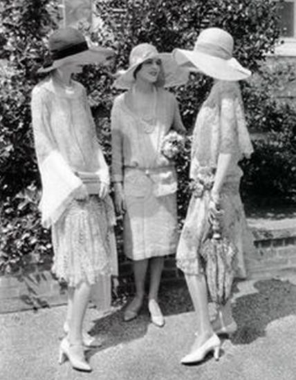Three women standing on the sidewalk chatting wearing 1920s daywear