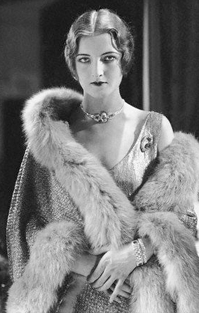 A 1920s woman wrapped in a fur coat looking pensive for a portait