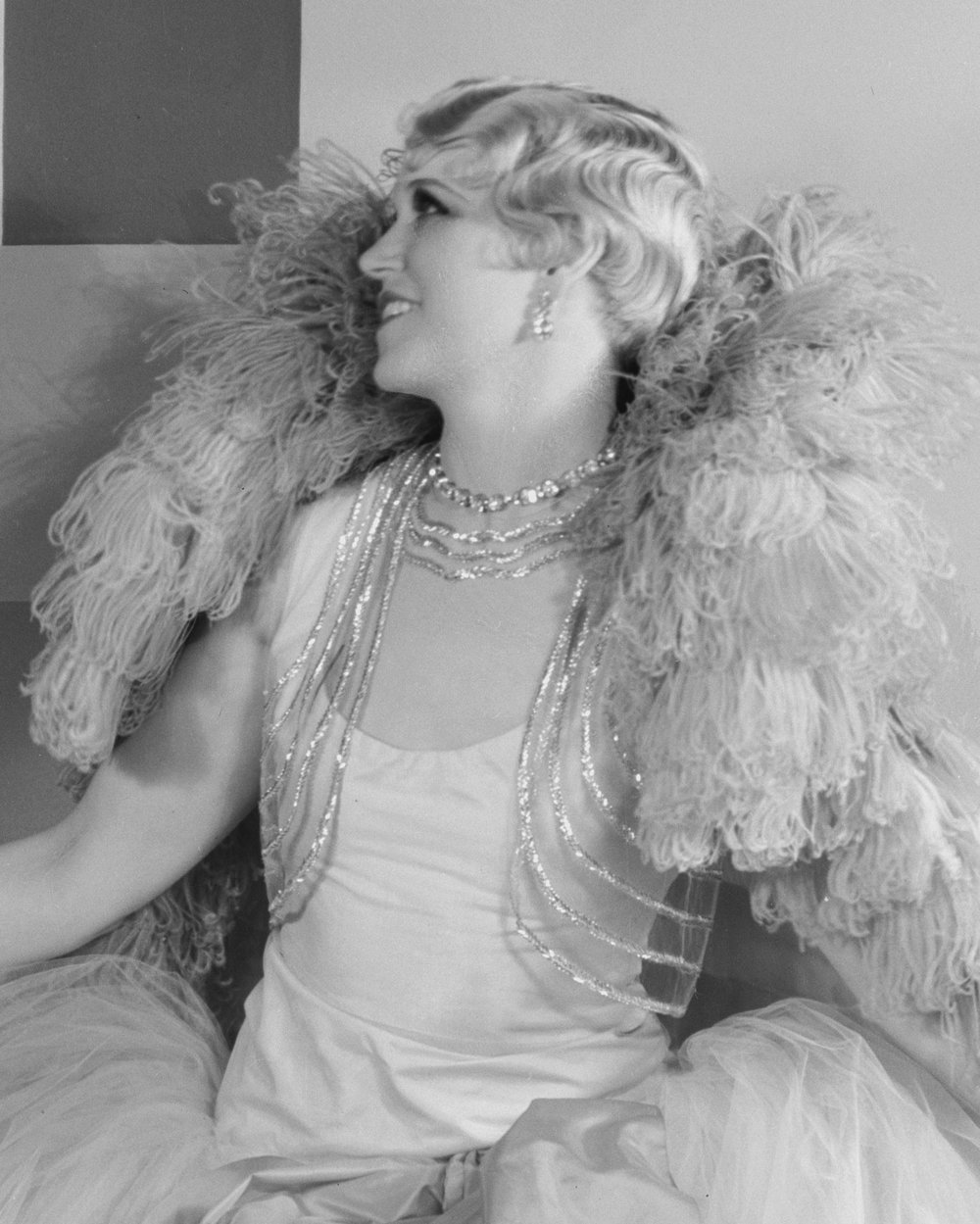 A 1920s woman in an ostrich feather cape and long draping jewelry