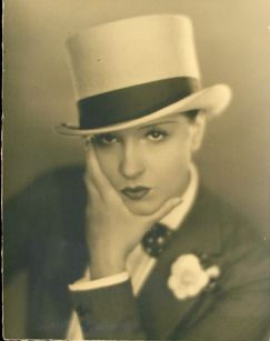An art deco era woman in a suit and white top hat