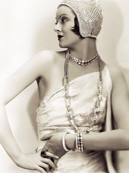 A woman in 1920s art deco era fashion wearing long jewelry