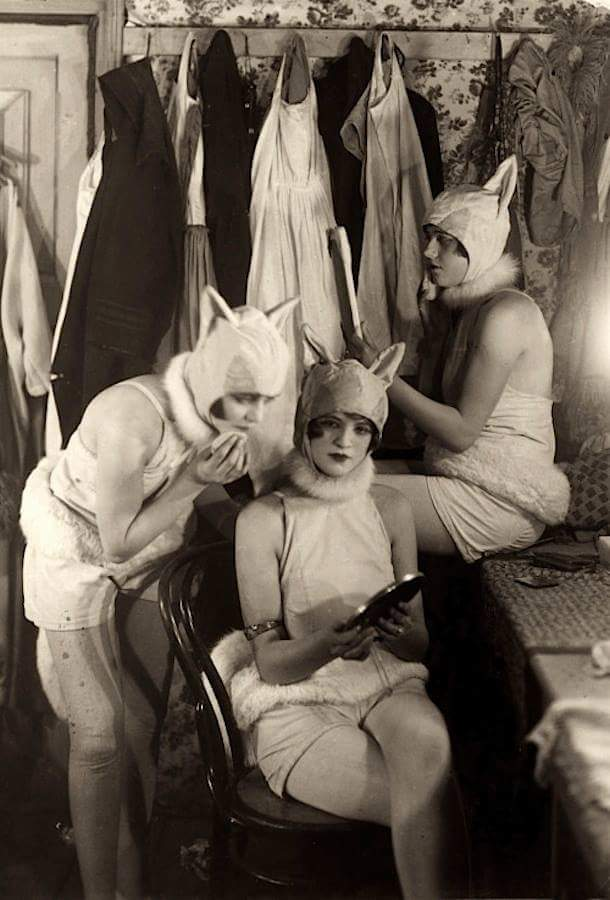 Three women in art deco era cat costumes sitting in the dressing room backstage