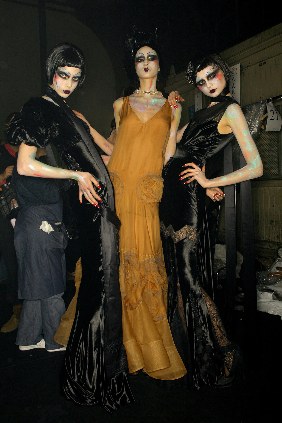 Three tall and slender women in art deco era costume and dark eye makeup
