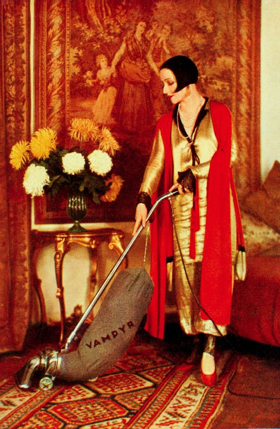 A woman in 1920s art deco era dress pushing a vacuum cleaner that says Vampyr on it