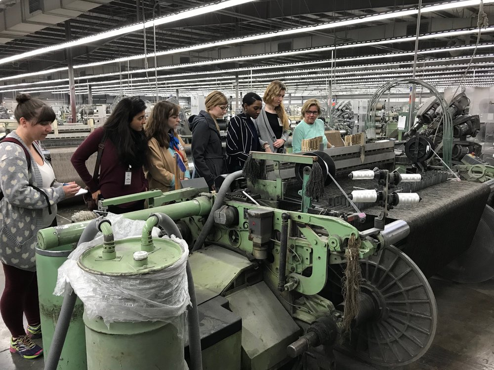 A group of students seeing firsthand how a loom works!