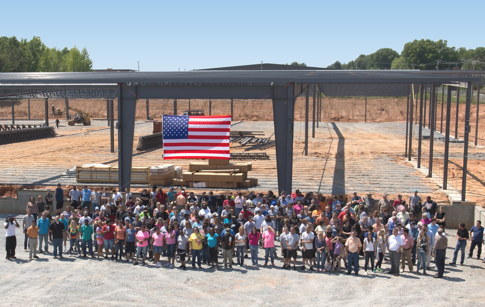 Above: A group of STI employees standing in front of their new 150,000 sq. ft. plant that opened in January 2018.