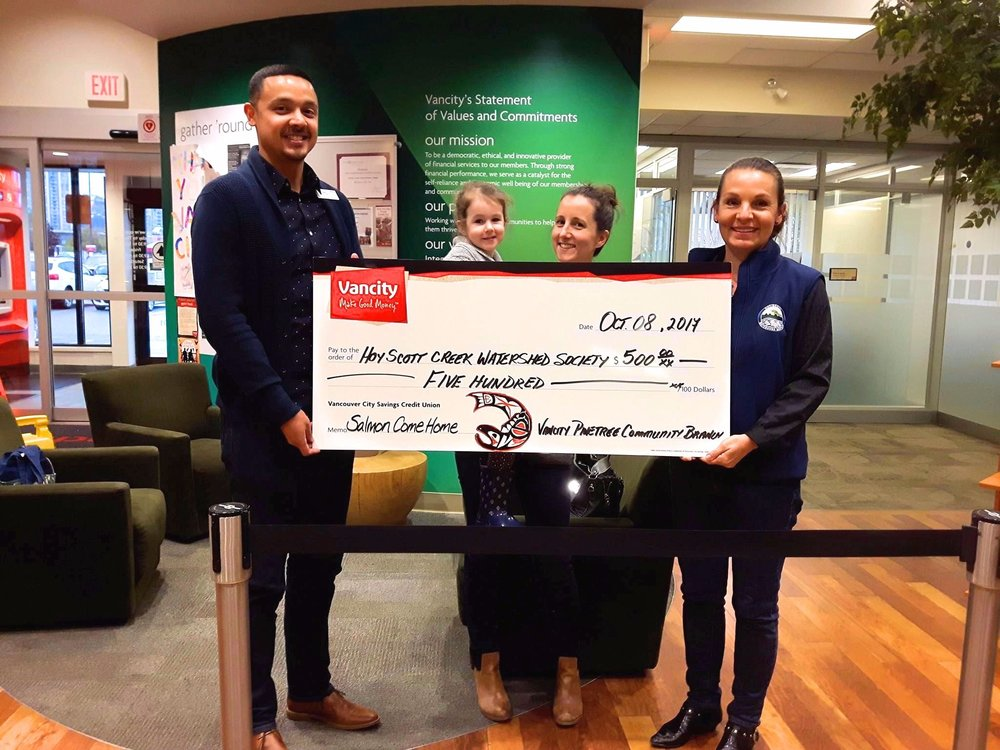 Vancity manager Omar (left) presents a $500 cheque to HSWS secretary Emily (center with daughter Joan) and HSWS president Robbin (right) for Salmon Come Home.