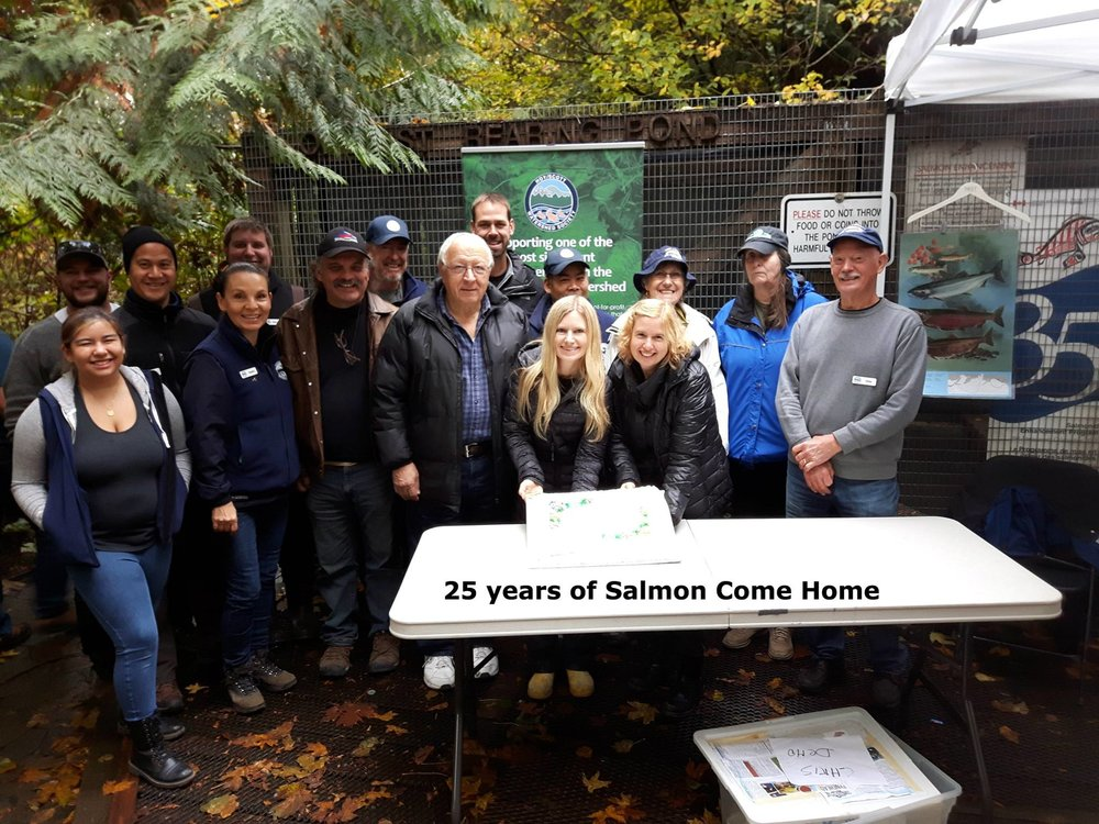 "25 years!  A group photo and cake to commemorate 25 years of ""Salmon Come Home.""  Seen left to right: Maya Uno (front), Tyler Thibault, Rodney Lee, Robbin Whachell (front), AJ Currie (back), Dave Bennie, Earl Elliott, Tony Matahlija, Scott Ducharme, Caresse Selk, Kyle Uno (back), Sandra Uno, Lilian Elliott (back), Dr. Elaine Golds, and Chris Hamming."