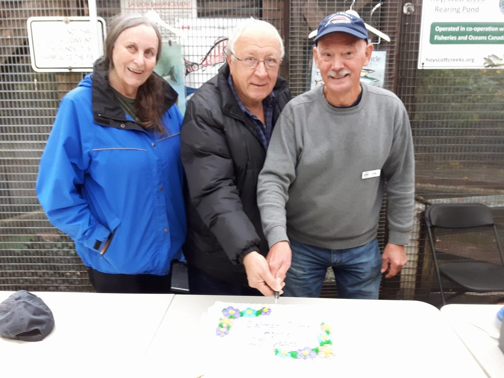 Cutting the cake for 25 years of Salmon Come Home - left to right: Dr. Elaine Golds of Burke Mountain Naturalists who have been coming to Salmon Come Home probably since day 1, Tony Matahlija from North Fraser Salmon Assistance Project, who helped build the hatchery, and HSWS founding member and salmon educator, Chris Hamming.