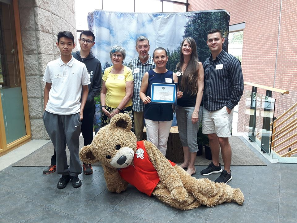Members of Hoy-Scott Watershed Society with their certificate of appreciation pose with Hucklebeary at Coquitlam city hall.