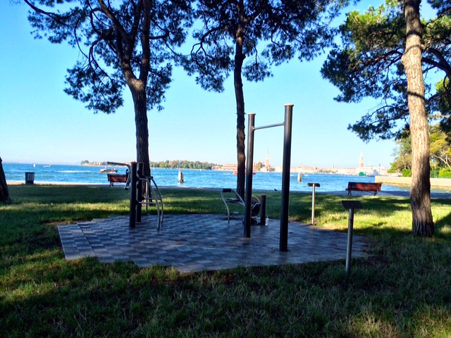 Outdoor gym equipped with a pull-up bar, dips/abs bars, and a bike. Parco delle Rimembranze in Venice, Italy.