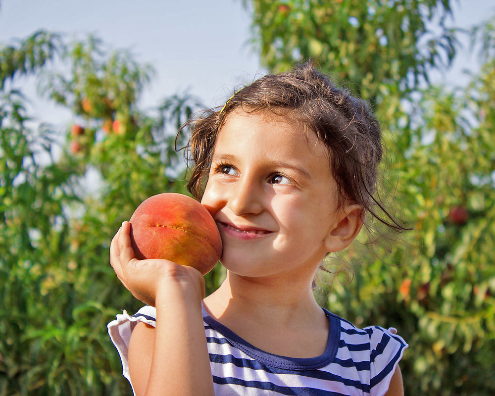 Photo of girl holding a peach.