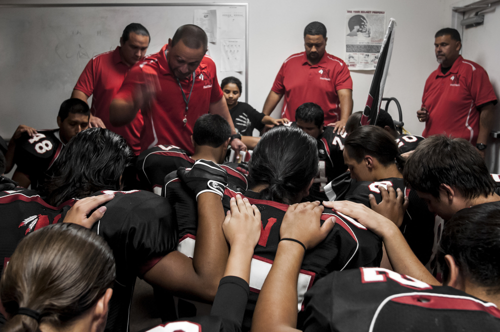 SAN JACINTO, Calif. -- Noli Braves' head coach Clyde Miller says a motivational prayer to his football team in the locker room before the start of their third home game in Noli Indian School field, Friday, Oct. 5, 2012. (Photo by Jonathen E. Davis/Brooks Institute ©2012)