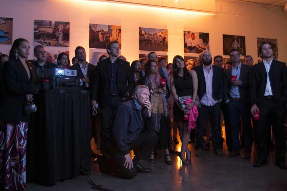 LOS ANGELES (April 6, 2013) – Academy Award winner John Voight (center) kneels as he watches a video about the work of disaster relief organization Team Rubicon (TR) during the Sunset on Salute fundraiser at Siren Studios, Saturday, April 6, 2013. Salute on Sunset is a fundraiser to honor, support, and congratulate the veterans and volunteers of TR. The organization unites the skills and experience of military veterans with first responders to rapidly deploy emergency response teams into crisis situations. TR offers veterans a chance to continue their service by helping and empowering those afflicted by disasters, and also themselves. (Photograph by Jonathen E. Davis)