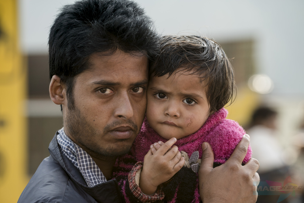 A father and daughter waiting in line for medical assistance.