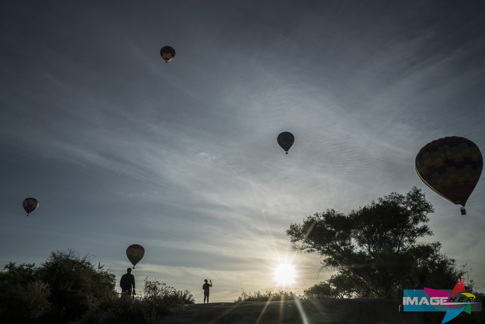 The sun and hot air balloons rise in the Temecula Valley skies in the early morning.