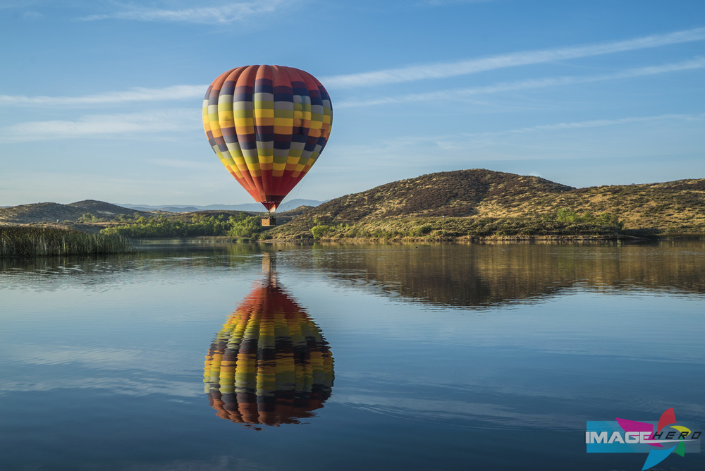 A single hot air balloon hovers over Lake Skinner in Temecula Valley.
