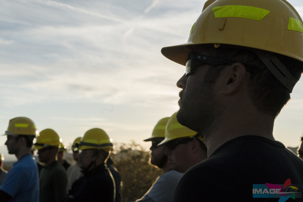 Team Rubicon member Adamo Don Vito and other members listen to their action after review (AAR) after finishing their field training exercise for Fire Fighter Type 2.