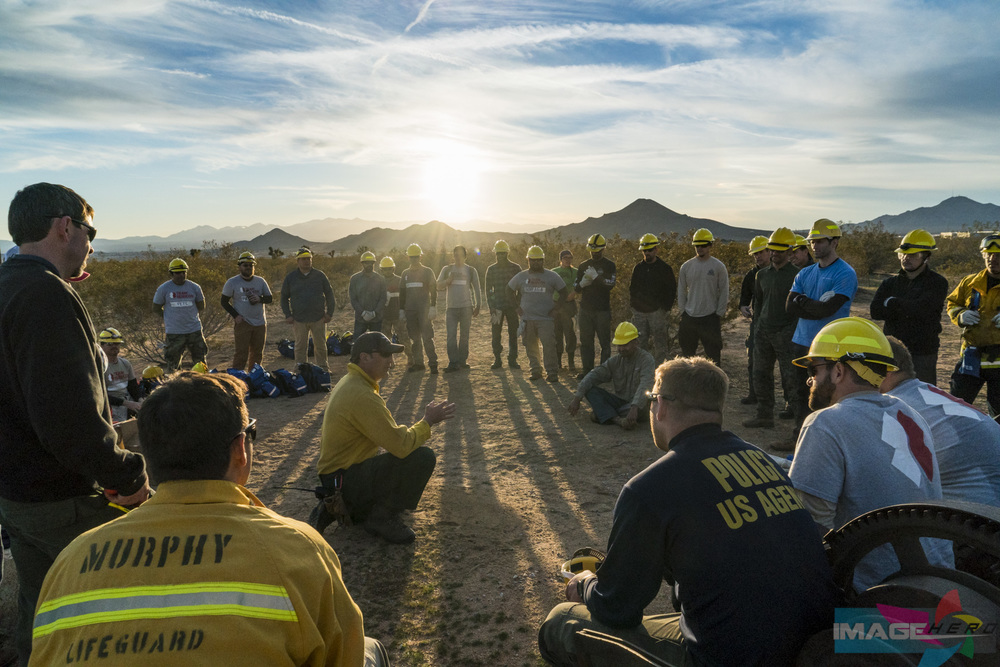 Team Rubicon Wildland Firefighter lead instructor Phil Lind (center) gives an after action review (AAR) to the entire team after they successfully completed field training exercise for Fire Fighter Type 2.
