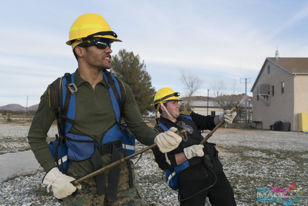 Team Rubicon members Anthony Lewis (left) Jordan Zeitlin practice using backpack fire pumps during a field training exercise for Fire Fighter Type 2.